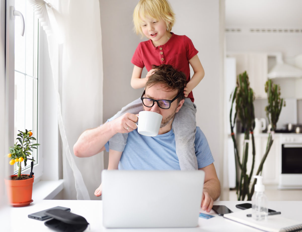 man working on a laptop at the kitchen table with toddler on his shoulders