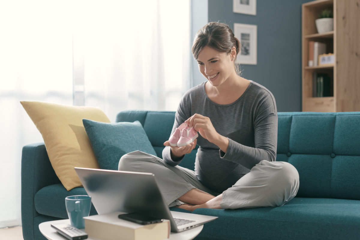 Happy White pregnant woman sitting cross-legged on a sofa while holding baby shoes taking part in a virtual baby shower game