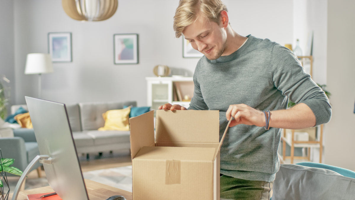 Blond haired White man opening a box with materials for a virtual reunion avtivity.