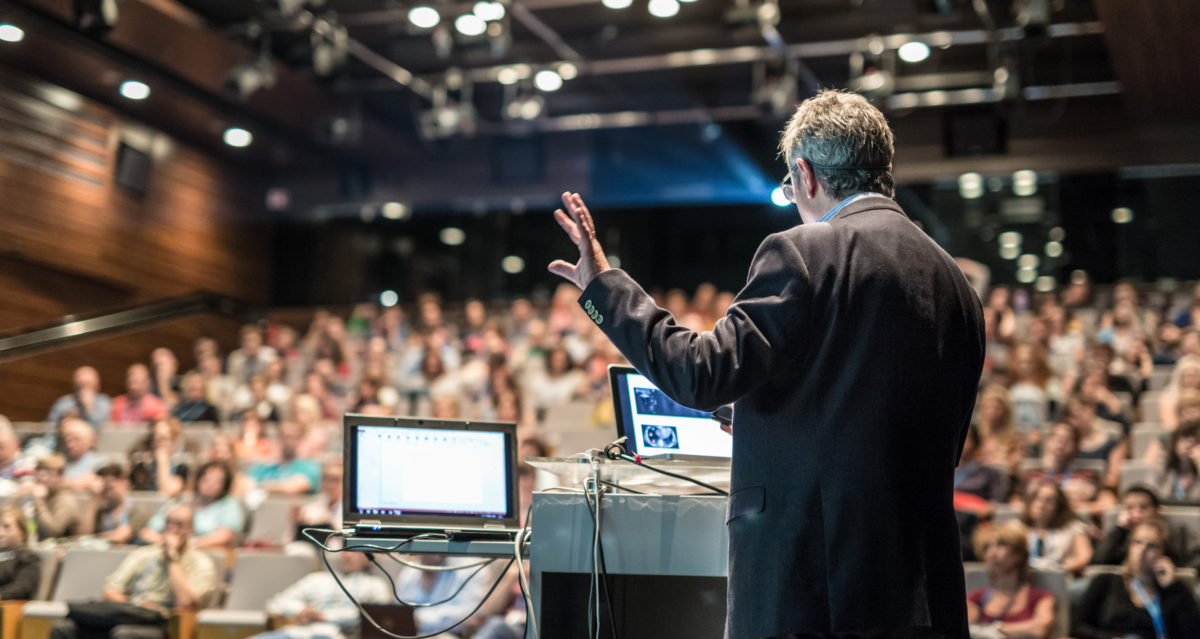 Back view of a man presenting on stage at a hybrid event with two monitors
