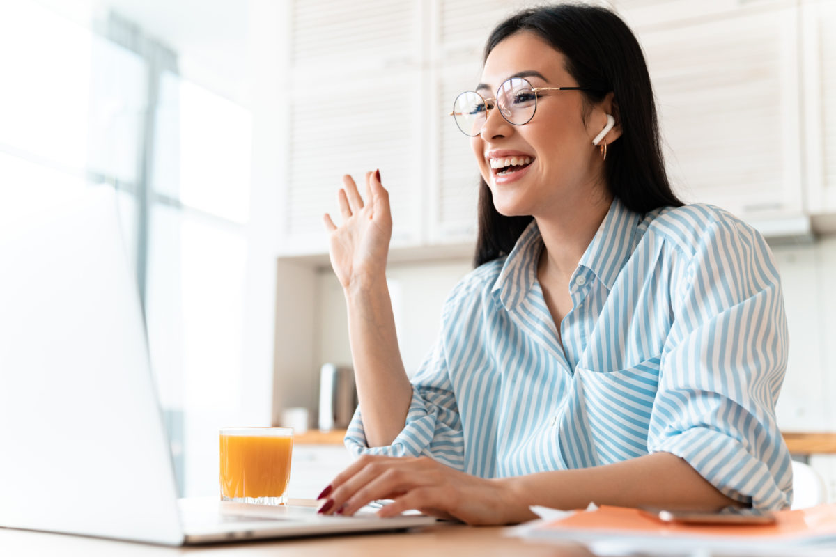 Young woman participating in a virtual college class reunion marketing committee meeting, waving hello