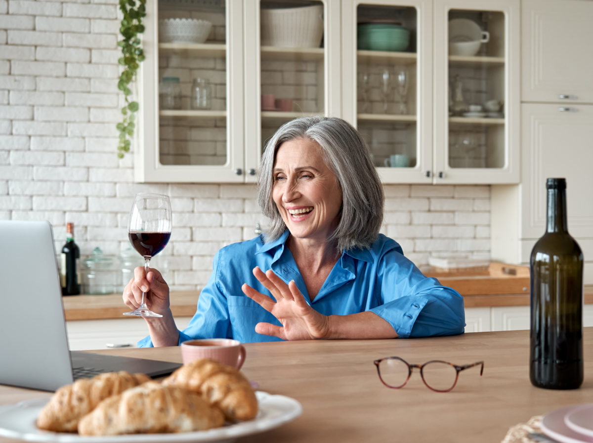 Happy 60s mature woman drinking wine as part of a virtual college class reunion