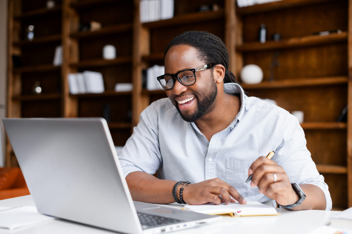 Black man sitting at a desk in front of a bookcase, using a laptop for a video conference call to plan a college reunion