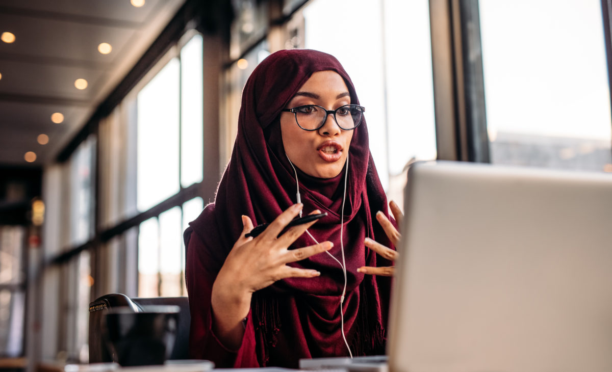 Businesswoman in hijab interacting at an online conference from her laptop