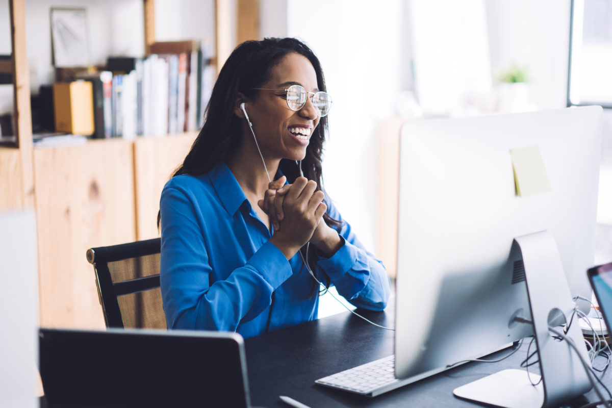 Black woman attending a virtual event from her home office